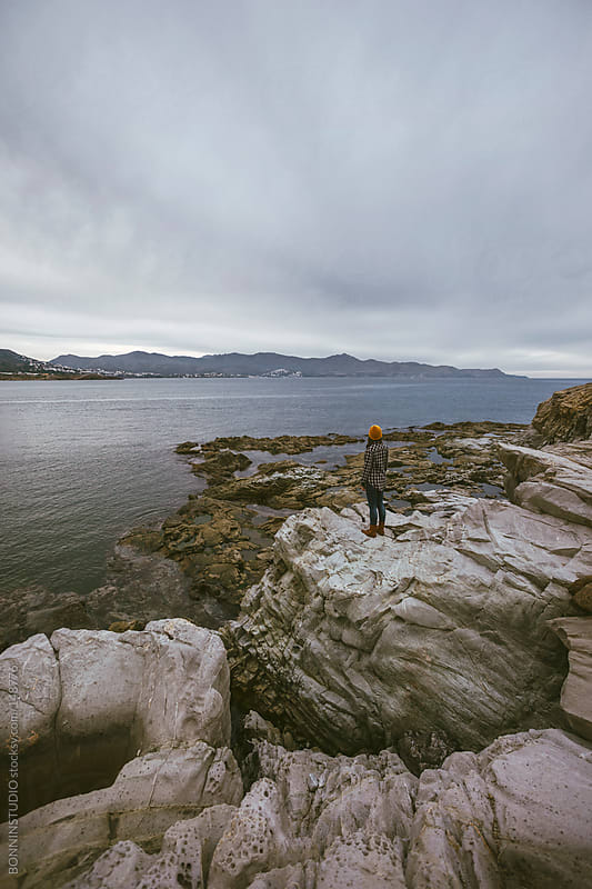 Woman looking the sea from the rocks. by BONNINSTUDIO for Stocksy United