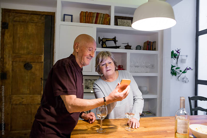 Elderly couple using their phone whilst drinking wine at home. by BONNINSTUDIO for Stocksy United