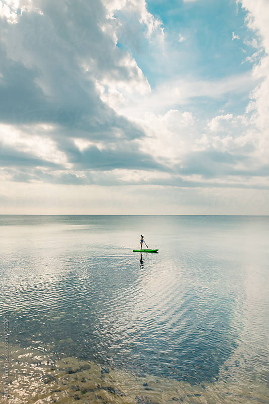 teen girl playing on kayak in the sea by Gillian Vann for Stocksy United