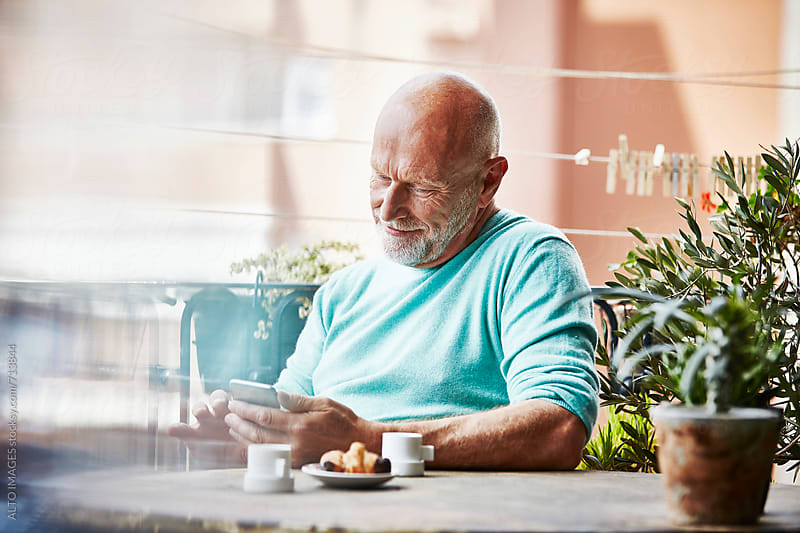 Happy Senior Man Using Mobile Phone On Balcony by ALTO IMAGES for Stocksy United