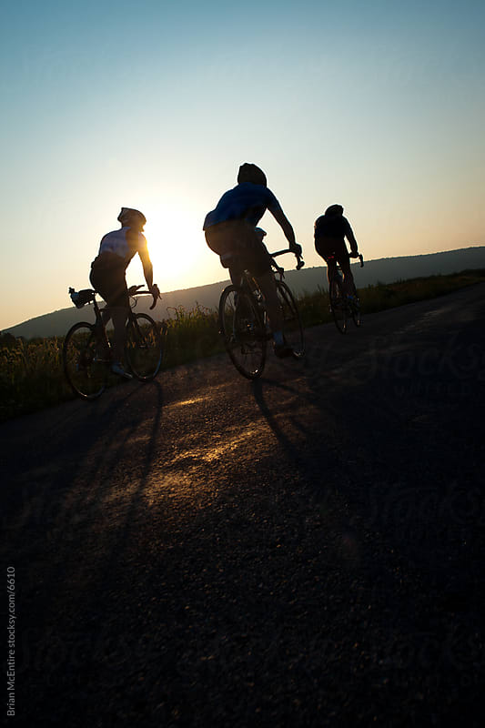 Silhouetted Cyclists Climbing Rural Roads at Sunset by Brian McEntire for Stocksy United