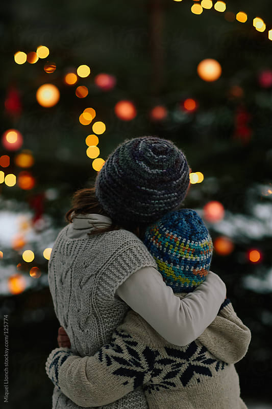 Two children embracing each other and looking at christmas tree with lights at night by Miquel Llonch for Stocksy United