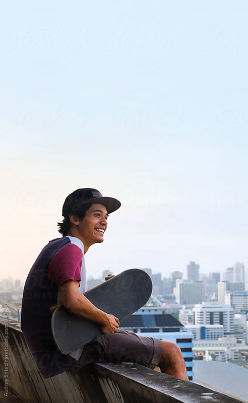 Urban young skateboarder sitting on top of the building with cityscape in background. by Marko Milanovic for Stocksy United