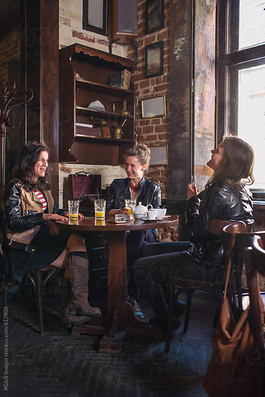 Young women in leather jackets talking in a pub by RG&B Images for Stocksy United