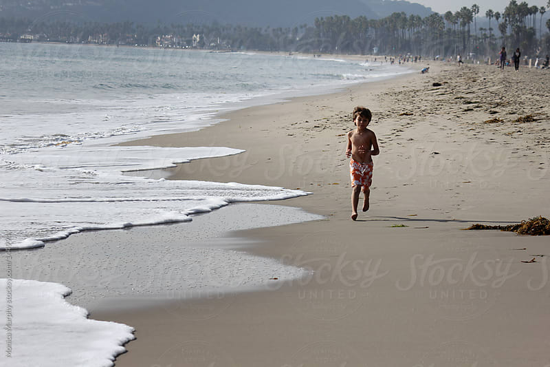 Young boy runs along beach by the seashore by Monica Murphy for Stocksy United