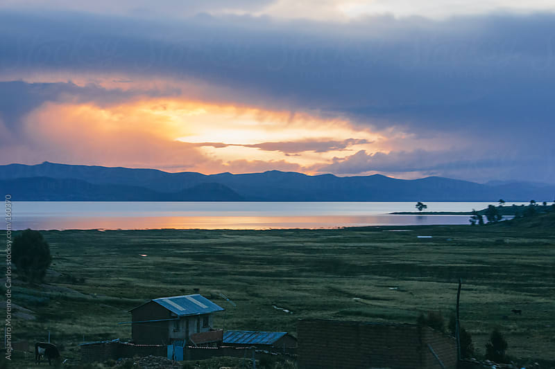 Sunset on a lake with mountains, Titicaca, Bolivia by Alejandro Moreno de Carlos for Stocksy United