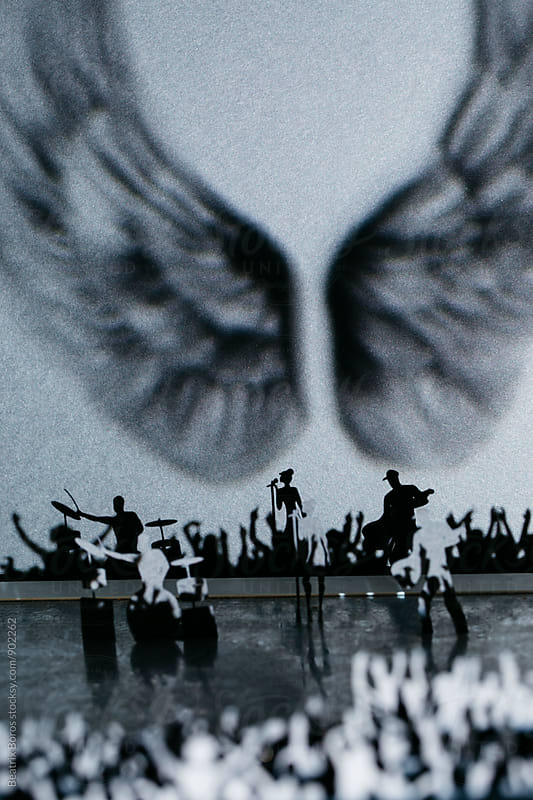Rock concert with huge wings on the wall by Beatrix Boros for Stocksy United