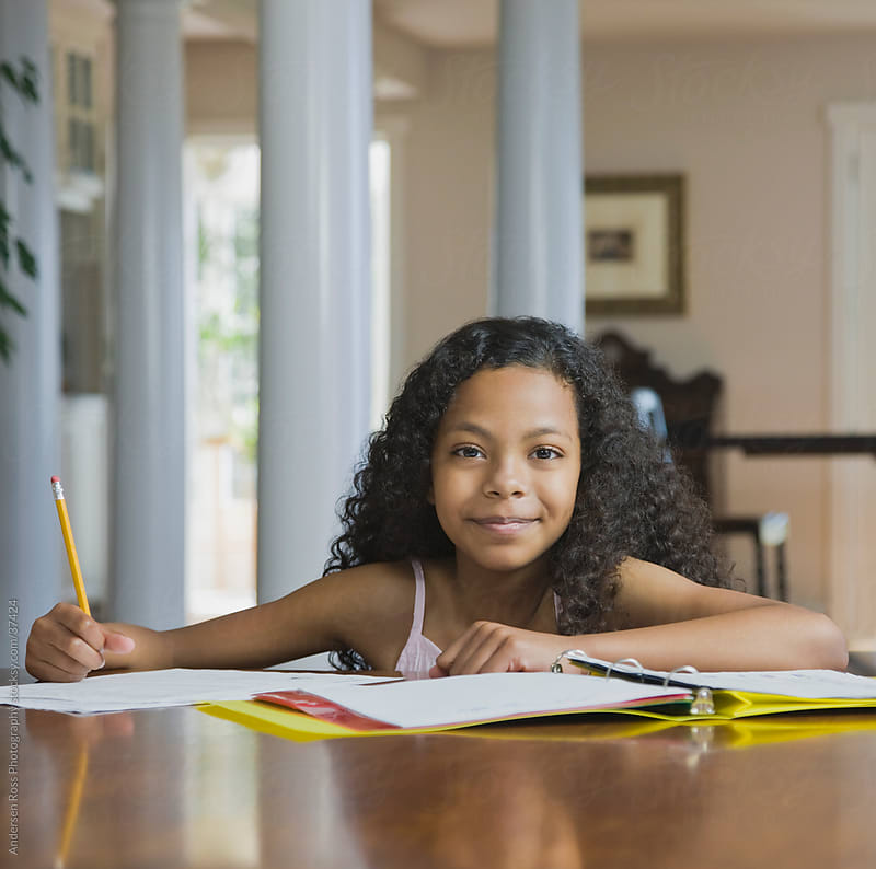 Portrait of smiling girl (12-13) doing homework  by Andersen Ross Photography for Stocksy United