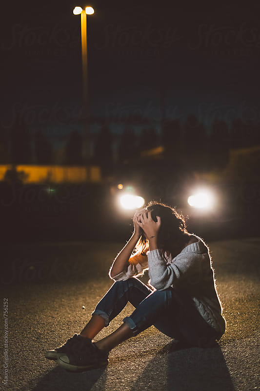 Woman sitting in front of a car at night by Mauro Grigollo for Stocksy United