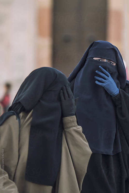 two traditional Muslim women in Medina,North Africa  hiding their faces from the camera by Igor Madjinca for Stocksy United