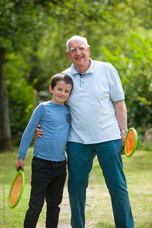 portrait of grandfather and grandson with tennis rackets by Lee Avison for Stocksy United