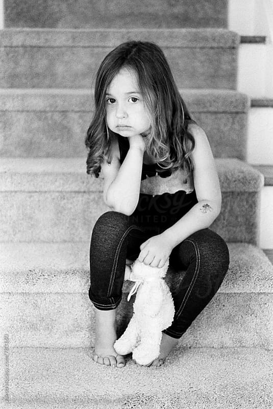 Beautiful young girl sitting on stairs of her home holding a teddy bear by Jakob for Stocksy United
