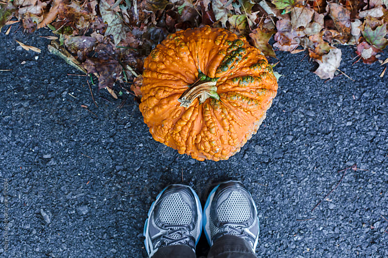 Feet standing in front of a pumpkin with warts. by Holly Clark for Stocksy United