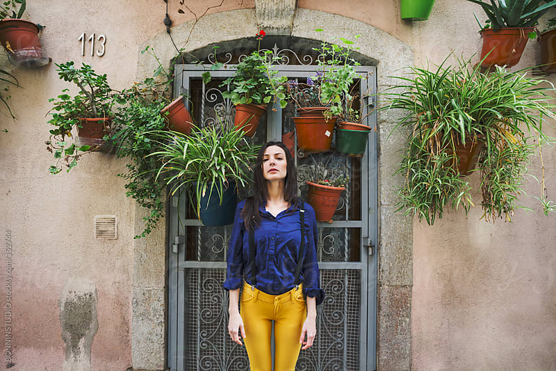 Woman standing in front a house with a lot of plants hanging. La Barceloneta, Barcelona. by BONNINSTUDIO for Stocksy United