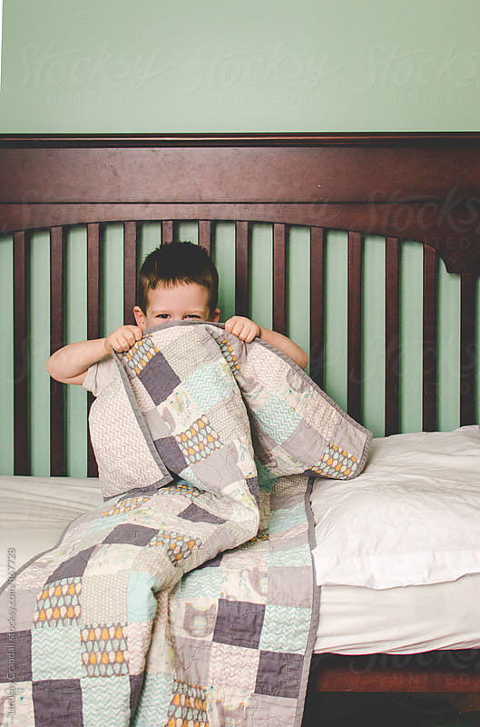 Small child peeking out from behind a quilt by Lindsay Crandall for Stocksy United
