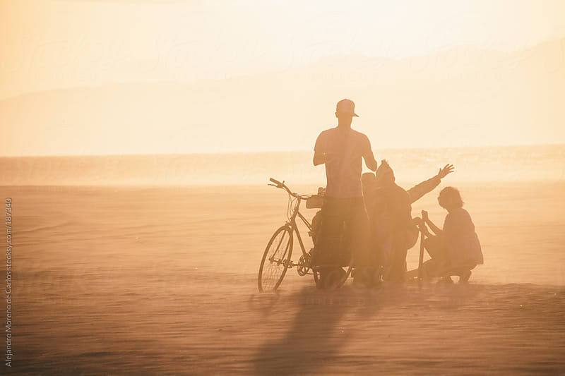 Group of trendy friends on the beach at sunset. People silhouette by Alejandro Moreno de Carlos for Stocksy United