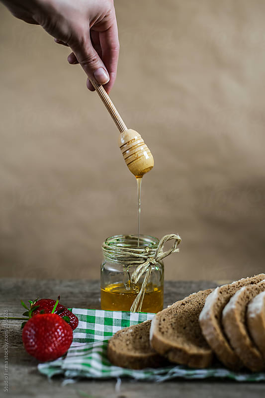 Bread and honey on the table with strawberries by Studio Firma for Stocksy United