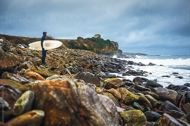 Surfer looking at the ocean by David Sciora for Stocksy United