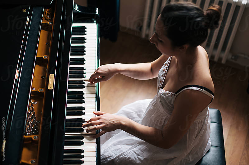 Woman playing piano  by Marija Mandic for Stocksy United