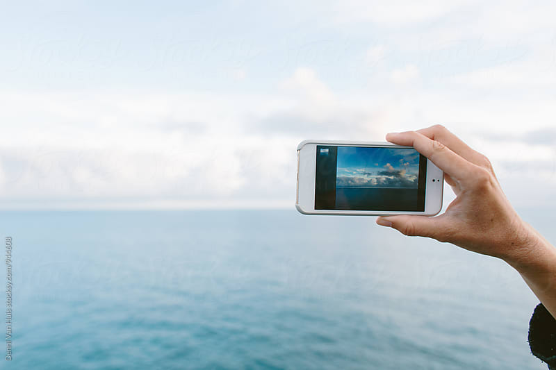 Hand holding and using a smartphone with the ocean in the background by Denni Van Huis for Stocksy United