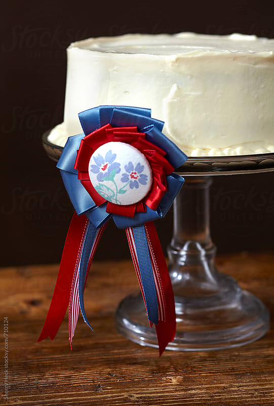 Vanilla frosted cake on glass cakestand with decorative prize ribbon by Sherry Heck for Stocksy United