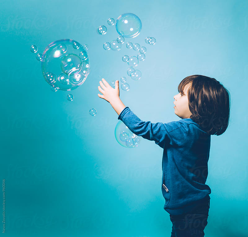 5 year old boy trying to catch soap bubbles by Nasos Zovoilis for Stocksy United