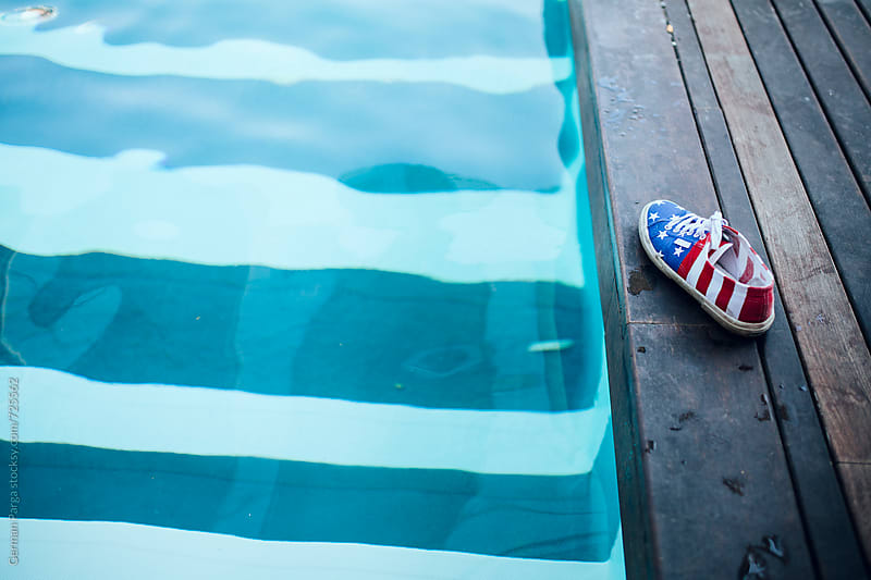 Bars and Stripes shoe next to a pool by German Parga for Stocksy United