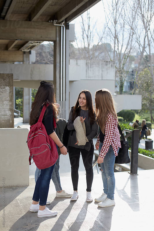 Group of young woman students talking  in the campus by Miquel Llonch for Stocksy United