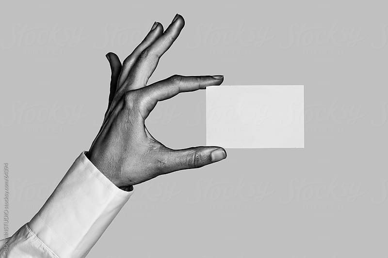 Business hand holding business blast. Black and white photo. by BONNINSTUDIO for Stocksy United