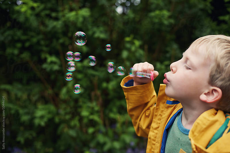 Child blowing bubbles by sally anscombe for Stocksy United