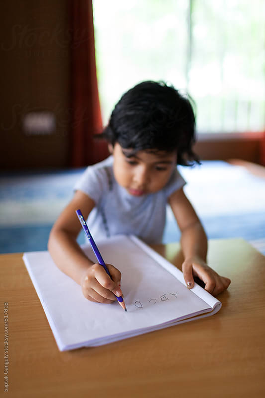 Little girl learning to write the english alphabets by Saptak Ganguly for Stocksy United