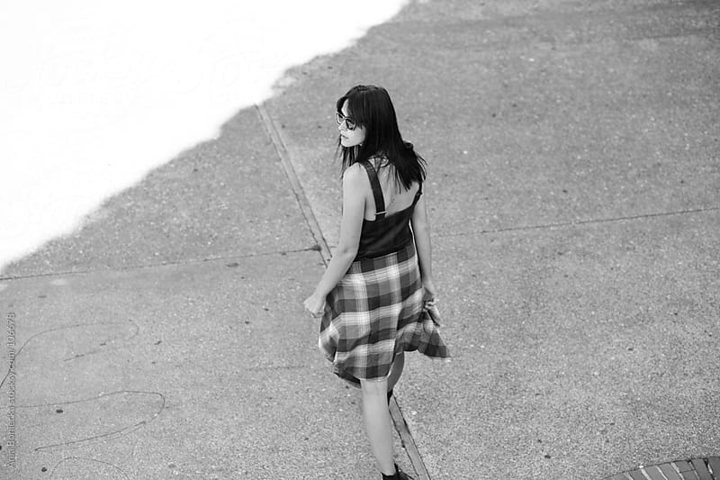 A woman walking away from camera on a street with a plaid shirt tied around her waist by Ania Boniecka for Stocksy United
