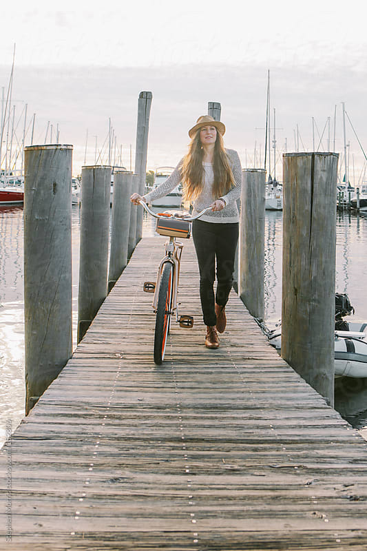 Woman with bicycle on dock by Stephen Morris for Stocksy United
