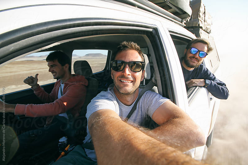 Three young men taking a self portrait through the window of an off-road car during adventure travel by Alejandro Moreno de Carlos for Stocksy United