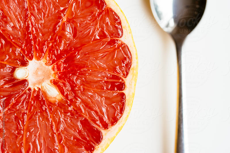 Grapefruit and spoon by Harald Walker for Stocksy United
