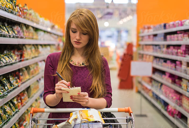 Woman Checking Shopping List in a Supermarket by Mosuno for Stocksy United