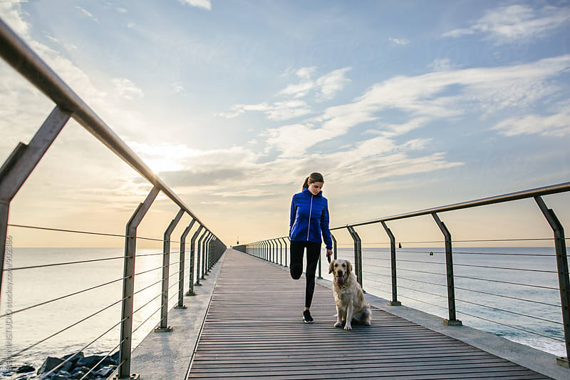 Woman doing stretching exercises with her dog on the bridge. by BONNINSTUDIO for Stocksy United
