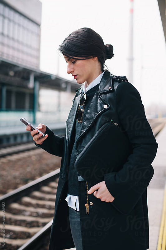 Woman browsing on her mobile phone on train station by Marija Mandic for Stocksy United