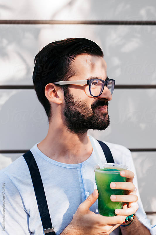 Young man making funny faces while drinking slush by Pixel Stories for Stocksy United