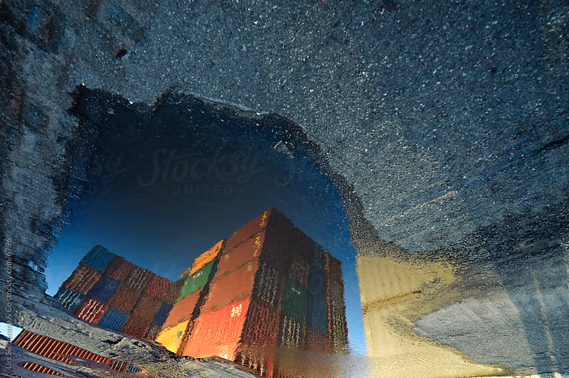 Container reflection in puddle by Urs Siedentop & Co for Stocksy United