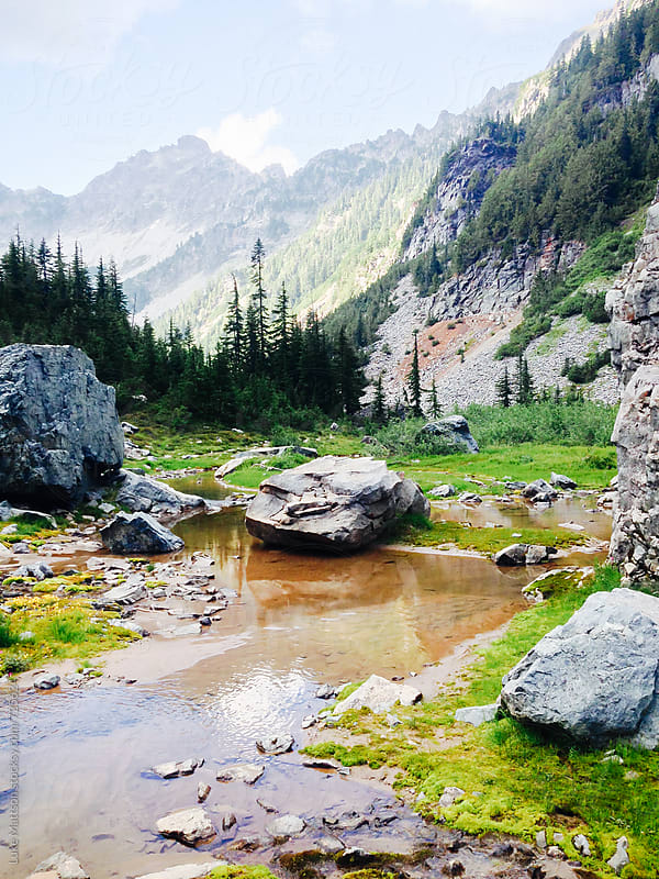Clear Pool Of Water Surrounded By Boulders In Mountain Meadow by Luke Mattson for Stocksy United