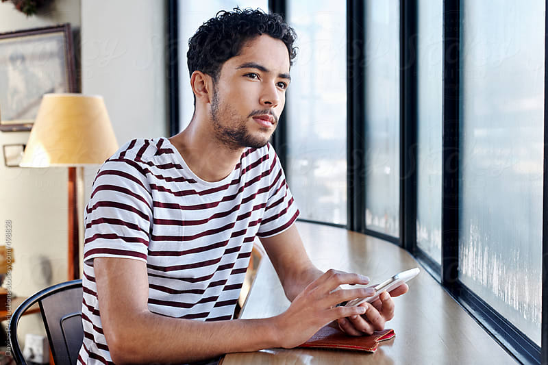 Mixed race man with tablet device in cafe  by Daxiao Productions for Stocksy United