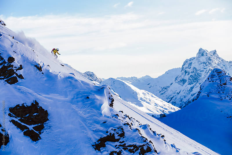 Man skiing steep mountain slope in powder snow with scenic background. by Søren Egeberg Photography for Stocksy United
