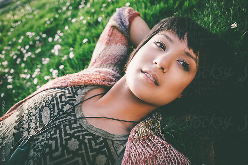 Beautiful woman lying down on the grass by Suprijono Suharjoto for Stocksy United