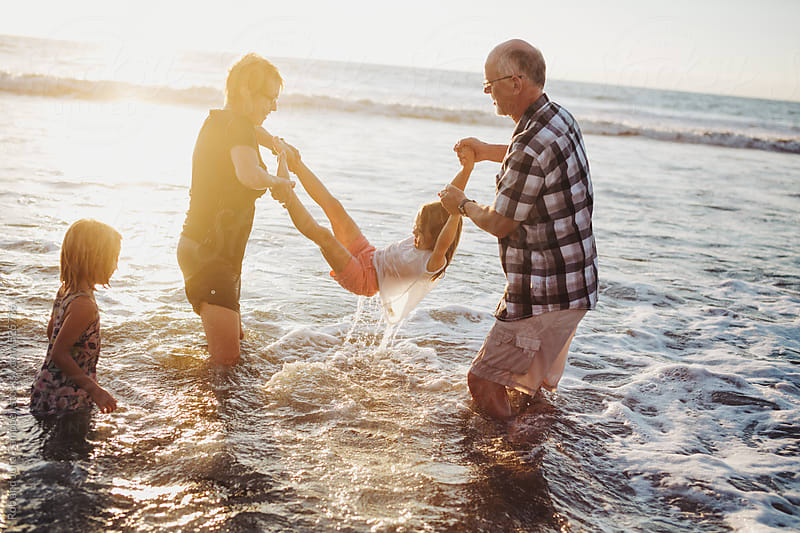 Fun, energetic grandparents playing in waves with young grandkids - girls - at sunset by Rob and Julia Campbell for Stocksy United