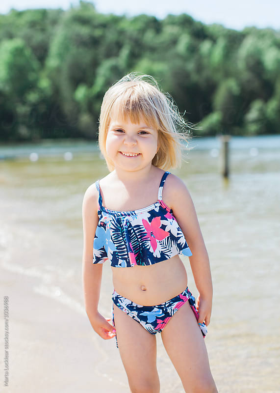 Little girl at the lake beach by Marta Locklear for Stocksy United