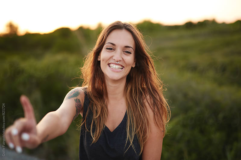 Portrait of young smiling woman outdoors by Guille Faingold for Stocksy United