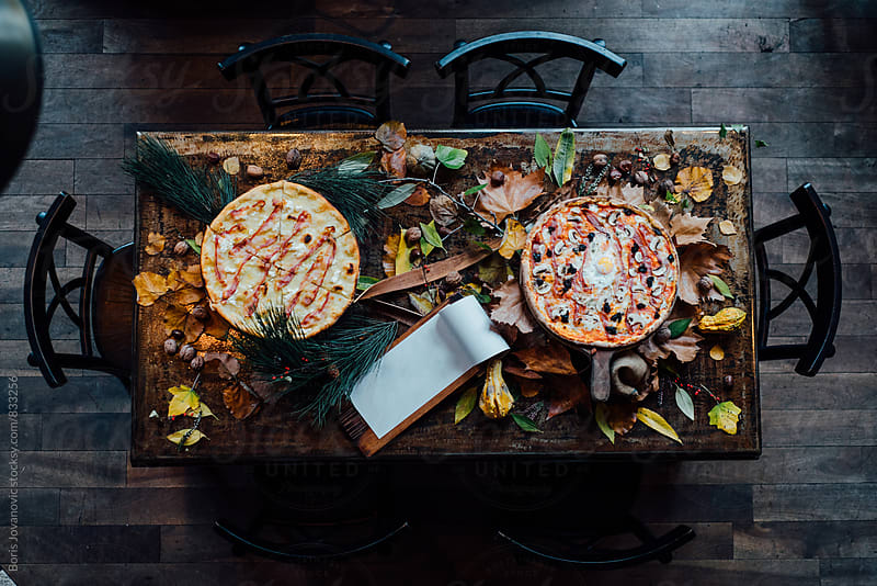 Above shot of table with two pizza by Boris Jovanovic for Stocksy United