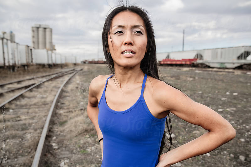 A fit woman in blue looking off camera by Shaun Robinson for Stocksy United