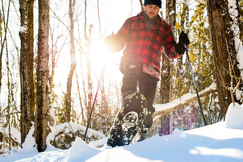 Man with Snowshoes in Winter Forest With Bright Sun by JP Danko for Stocksy United
